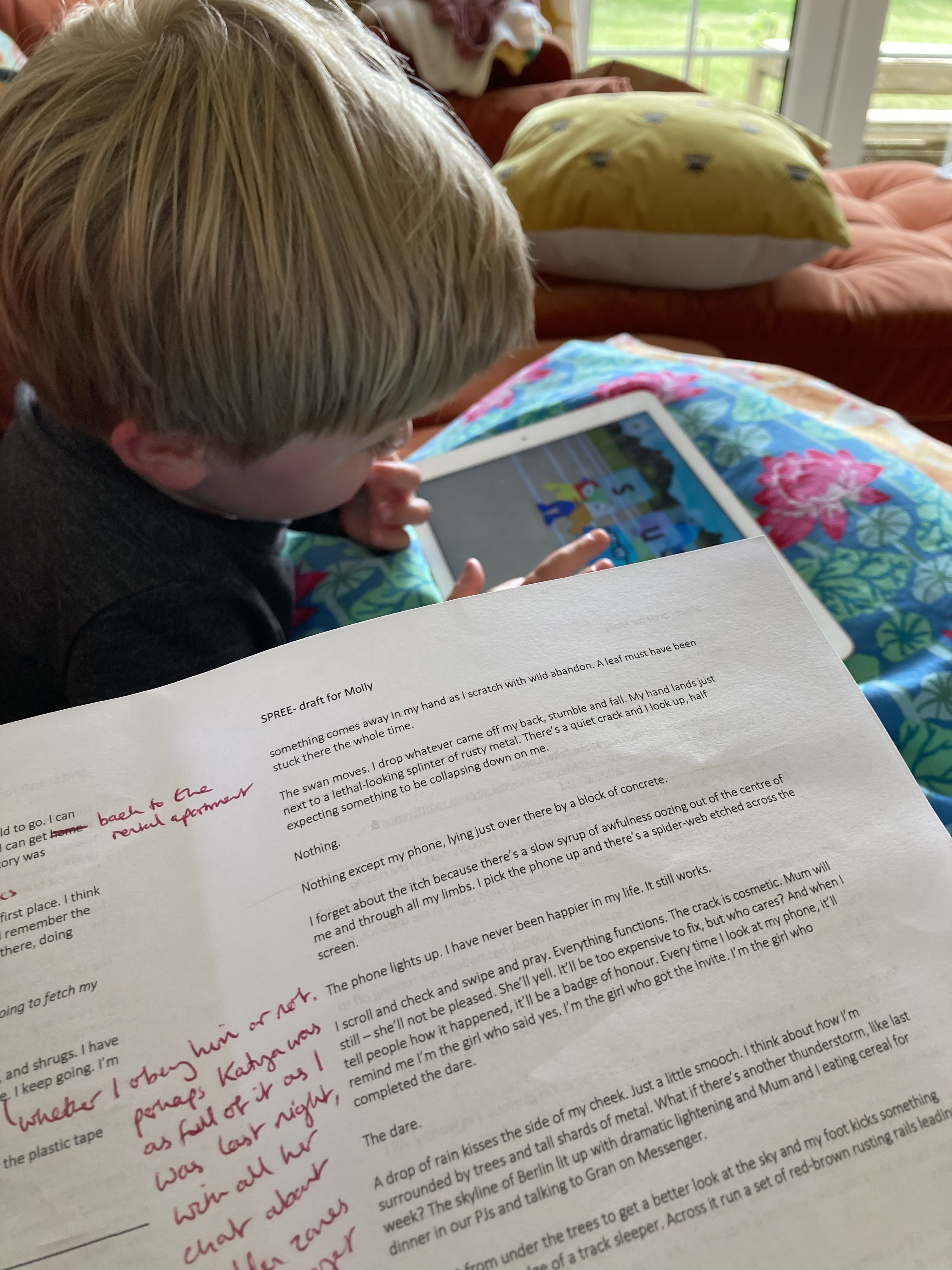 Printed story draft with red pen edits on it in the foreground, my son (blonde white toddler in dark grey top) playing on an iPad in the background