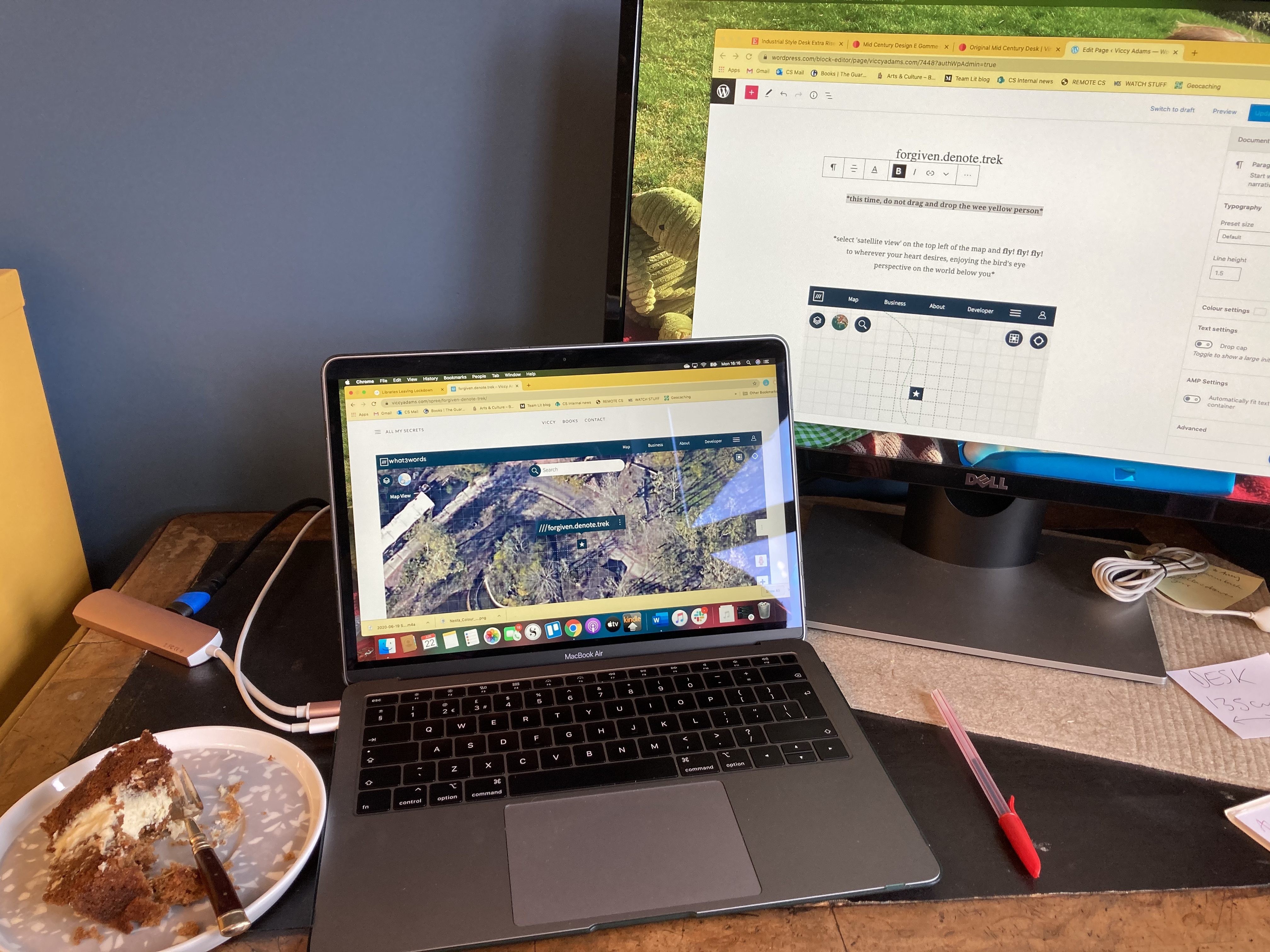 A close up photo of a dark blue room with a small dark wooden desk. In the centre of the deks is a Laptop showing a satellite view map, plugged into a monitor on the right-hand side showing a wordpress page being edited, and a plate of my birthday cake - a carrot cake delivered from an Edinburgh cafe called LoveCrumbs - on the left of the desk.